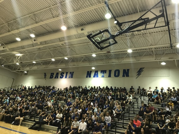 "Students sit in the bleachers at Thunder Basin High School's gym during the dedication ceremony for the school. The words ""BASIN NATION"" are written in blue on the wall above where they are sitting with thunderbolts painted on each side representing the new schools' mascot."