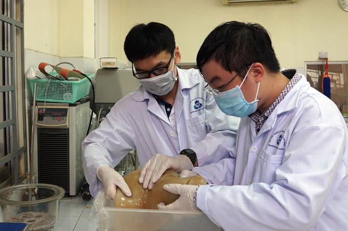Nhóm sinh viên kiểm tra lớp màng CNC được tạo ra từ bùn giấy trong phòng thí nghiệm.