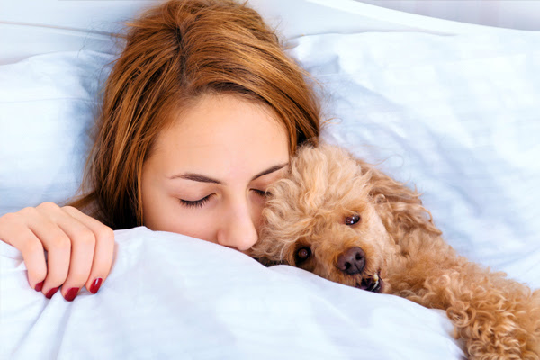 A woman sleeping with a dog.