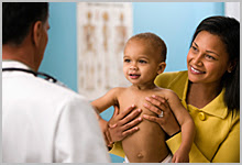 Mother holding a happy baby and talking with a doctor.