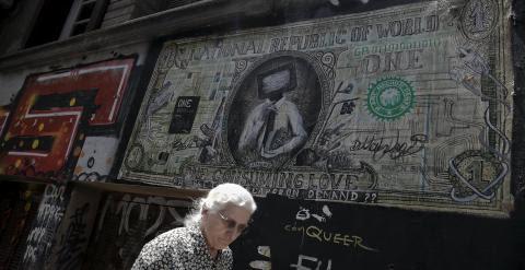 Una mujer pasa por delante de una pintada en Atenas que caricaturiza un billete de dólar. REUTERS/Alkis Konstantinidis