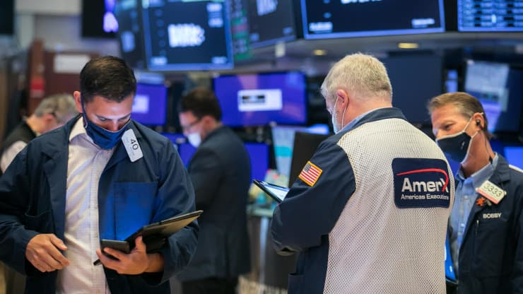Traders look down at their devices as they stand in a circle