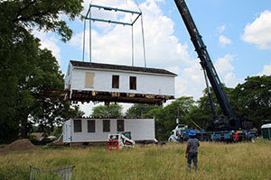 A crane lifts the second story off of a white clapboard house