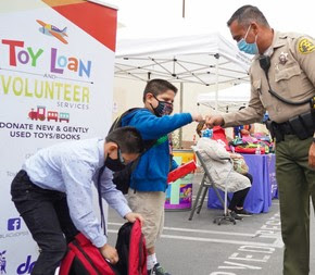 L.A. County Sheriff Department at Toy Loan Backpack Giveaway to give a Helping Hand