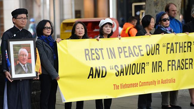 Members of the Vietnamese community hold signs aloft outside of Scots Church during the s