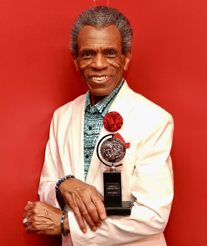 Andre De Shields holds a Tony Award in front of a red background while wearing a white suit.