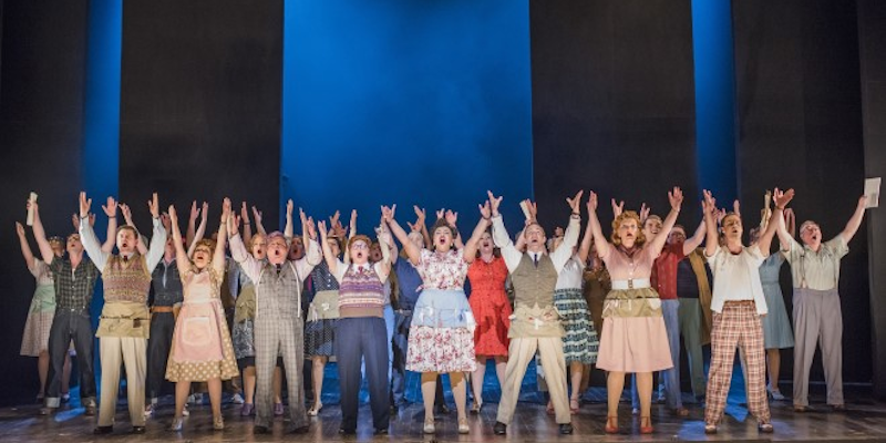 A chorus of singers on stage with their arms in the air
