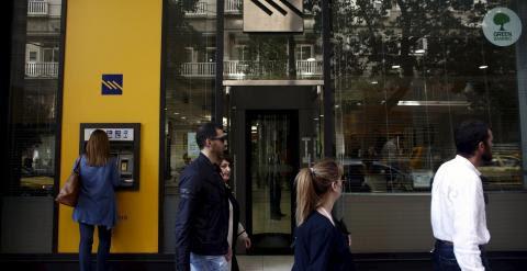 Una mujer usa un cajero del Banco Pireo en Atenas. /REUTERS