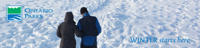 A man and women walking on a snow covered trail