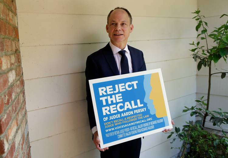 Judge Aaron Persky poses for a photo with a lawn sign opposing his recall in Los Altos Hills, Calif. (Jeff Chiu/AP)