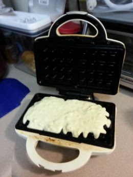 Waffle batter in the waffle iron.