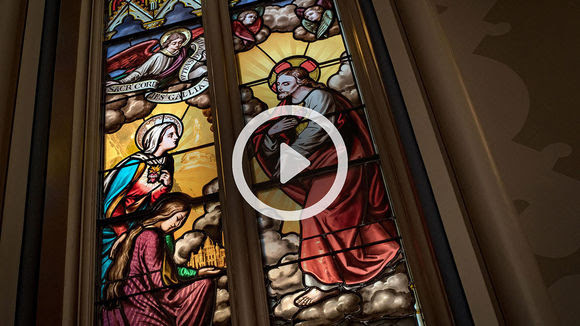 A play button over stained glass.