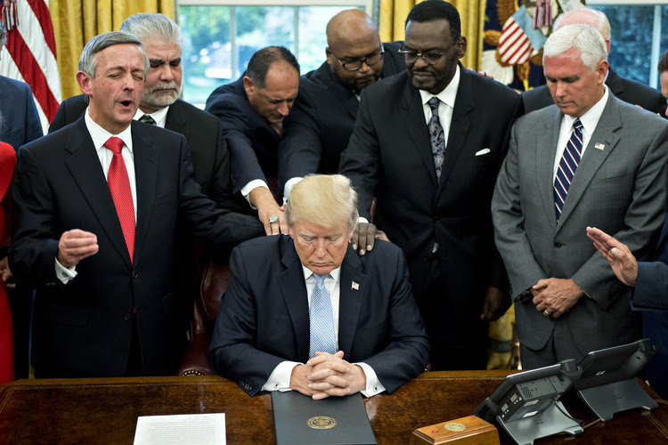 President Trump bows his head during prayer with faith leaders. (Andrew Harrer/Bloomberg News)