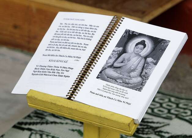 A book of mantras is open at a daily sunrise prayer session in front of a Buddhist altar erected at 11th Avenue and East 19th Street in Oakland, Calif. on Saturday, Sept. 13, 2014. Photo: Paul Chinn, The Chronicle