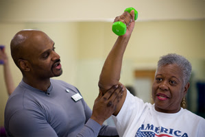 Elderly woman weightlifting with a coach