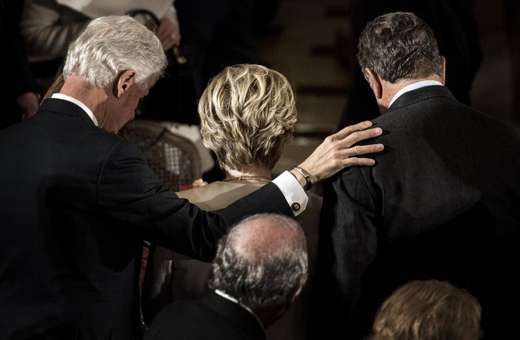 Bill and Hillary Clinton pray for Donald Trump at a luncheon after the inauguration. (Melina Mara/The Washington Post)