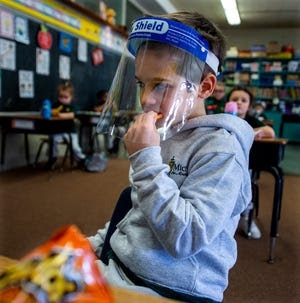 Kindergartner Michael  Engle, 5, of Levittown, keeps his face shield on while munching on cheese curls during snack time at St. Michael the Archangel School in Levittown, on Friday, Jan. 29, 2021.