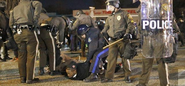 La policía detiene a un joven afroamericano durante las protestas en Ferguson