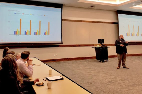 WDE Hathaway consultant, Bradley Barker, speaks to the Leadership Cheyenne class in a classroom at Laramie County Community College, with graphs projected on screens behind him.