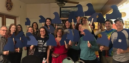 "Indivisible Yolo members hold ""blue wave"" signs at the General Meeting"