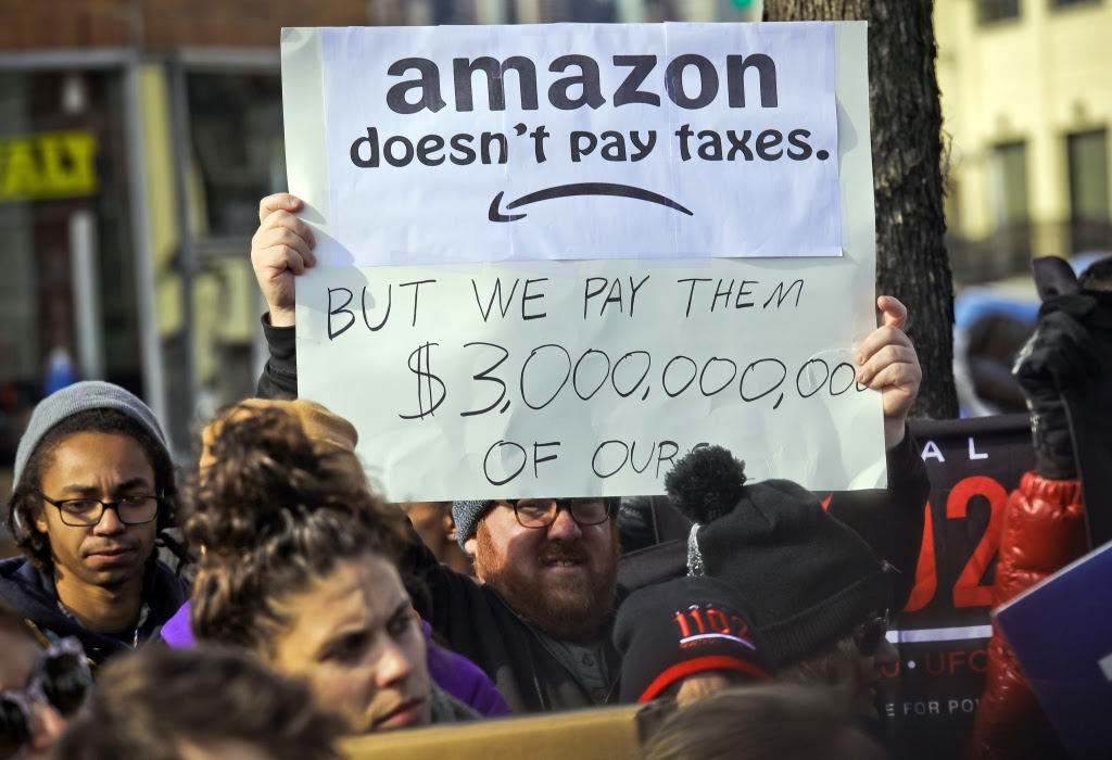 Protesters hold up anti-Amazon signs during a coalition rally and press conference of elected officials, community organizations and unions opposing Amazon headquarters getting subsidies to locate in Long Island City, in New YorkAmazon HQ Protest, New York, USA - 14 Nov 2018