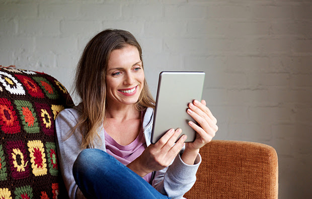 A woman sitting on a couch using a tablet.