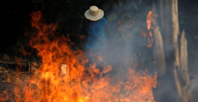 Un hombre trabaja en un tramo de la Amazonia en llamas. / Reuters