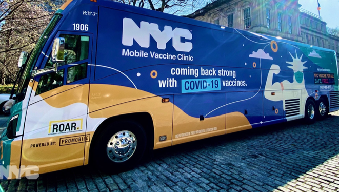Image of large passenger bus covered in blue yellow and white designs that say NYC Mobile Vaccine Clinic