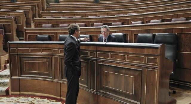 Alfonso Alonso y Alberto Ruiz-Gallardón conversan en el Congreso, prácticamente vacío. Archivo EFE.