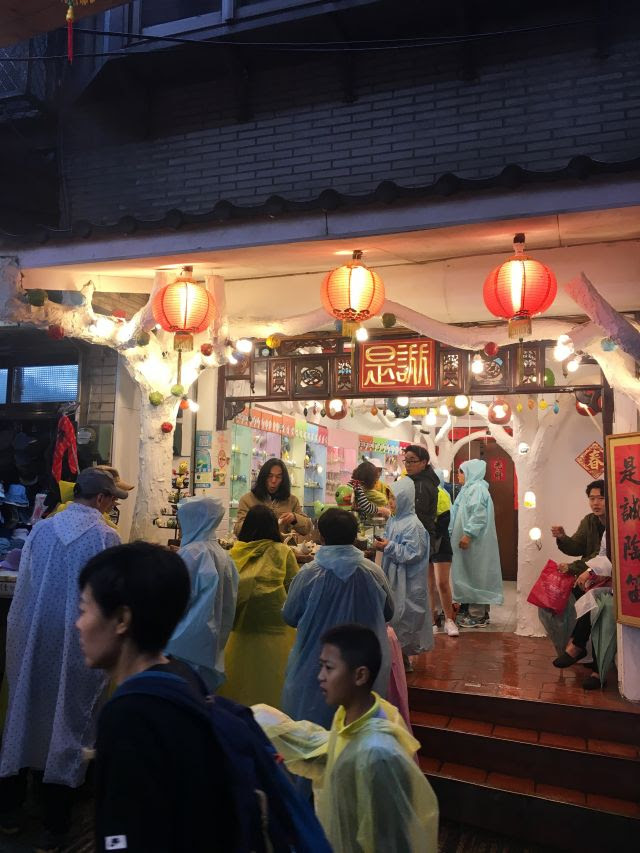ocarina shop in Jiufen, Taiwan, with red lanterns at the top and lots of tourists in pastel-colored rain ponchos milling around