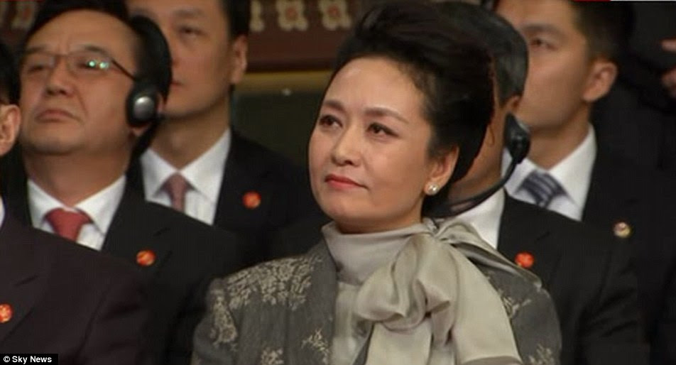 The president's speech was watched by his wife, Madame Peng, who changed outfits after her official welcome earlier in the day