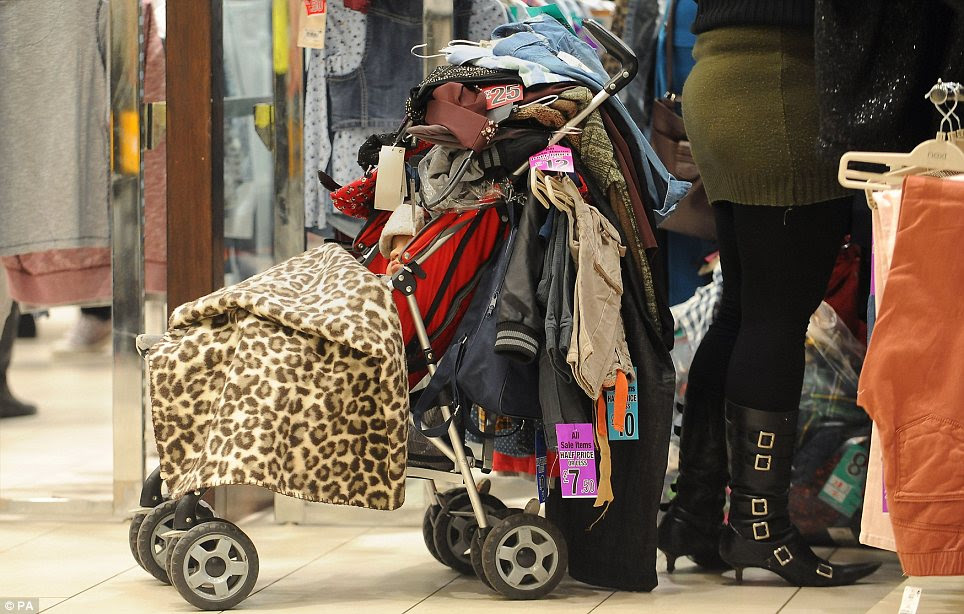 Engulfed: A baby in a pushchair which his mother has covered in clothes at the Highcross shopping centre in Leicester