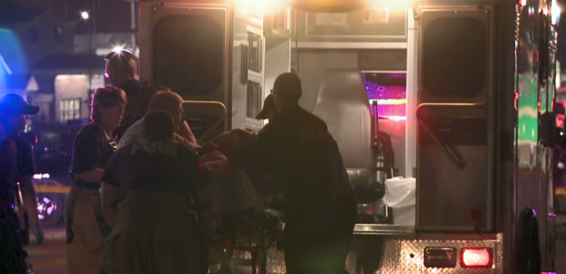 Screen shot of the video. EMTs loading a patient into the back of the ambulance