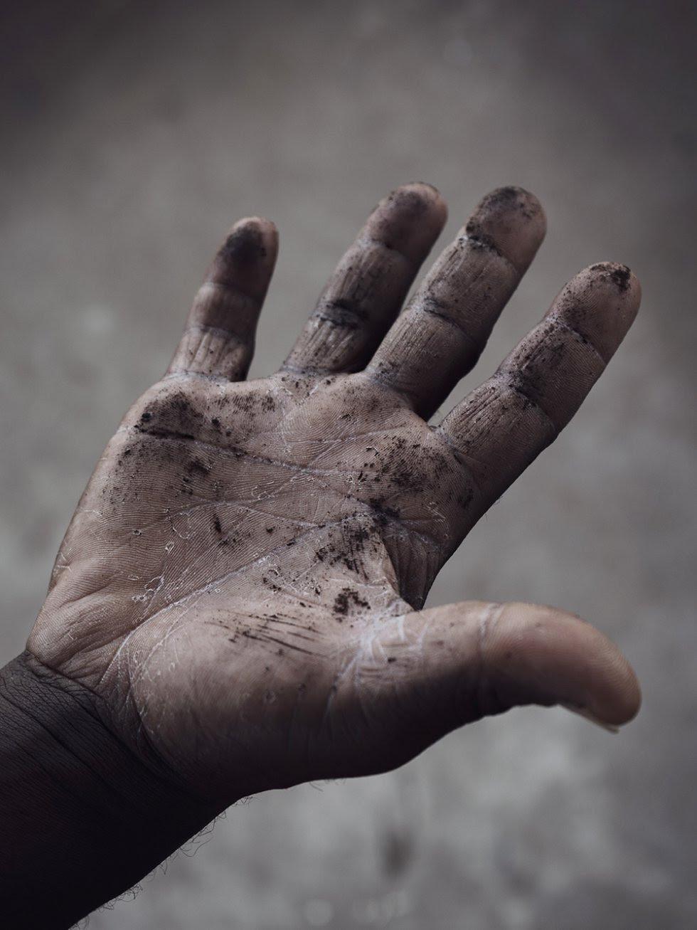El polvo fino del área de extracción termina en las casas de los pueblos. Edmundu muestra los residuos de carbón en la palma de su mano que se encuentran en su casa.