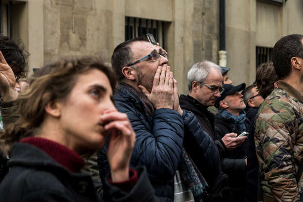 Slide 14 of 31: People watch the landmark Notre-Dame Cathedral burning in central Paris on April 15, 2019- A fire broke out at the landmark Notre-Dame Cathedral in central Paris, potentially involving renovation works being carried out at the site, the fire service said. (Photo by Nicolas Liponne/NurPhoto via Getty Images)