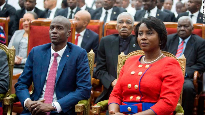 Moise and his wife sit together during a ceremony