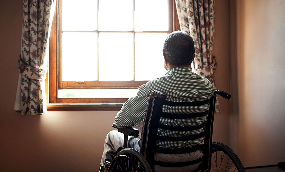 Man sitting in wheelchair and looking out a window