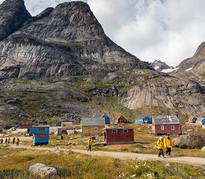 Passengers walk amongst Greenland houses