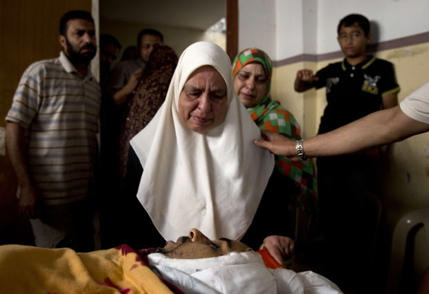 A relative of killed Palestinian doctor Anas Abu al-Kas, 33, mourns over his body during his funeral in the family home in the Jabalia refugee camp, in the northern Gaza Strip.