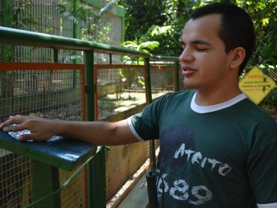 Fabrício França lê informações sobre os macacos do parque, na trilha com placas com texto em Braille e cordas para facilitar o percurso.
