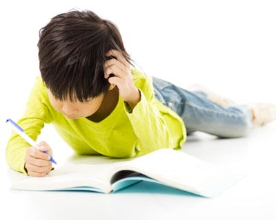 Photograph of a boy on the floor reading a book
