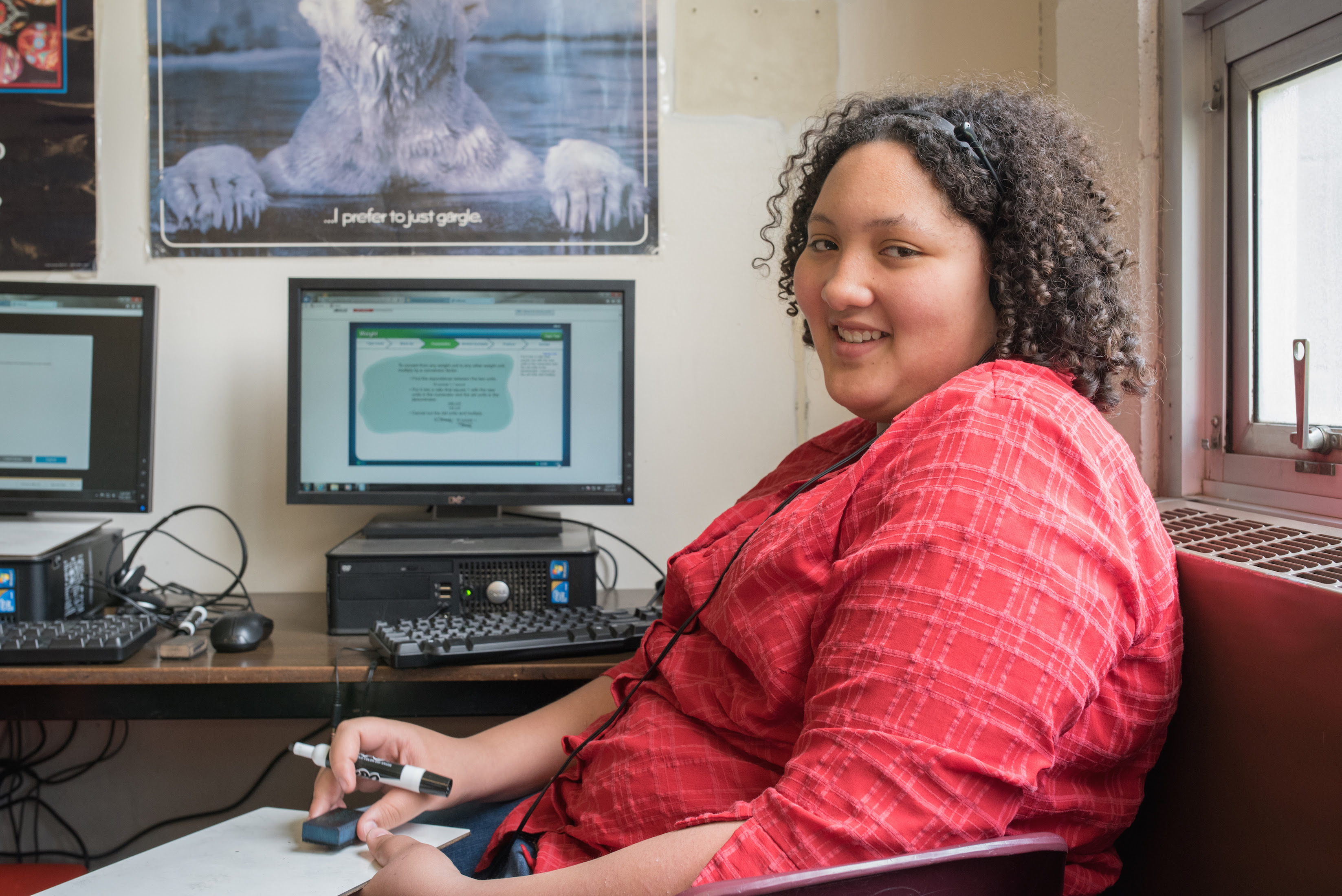 A student with curly short, dark hair in a red shirt is seated with a whiteboard in front of desktop computer displaying EdReady