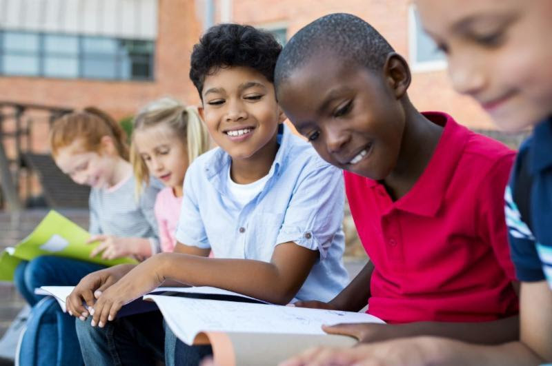 several students reading together outside a school building