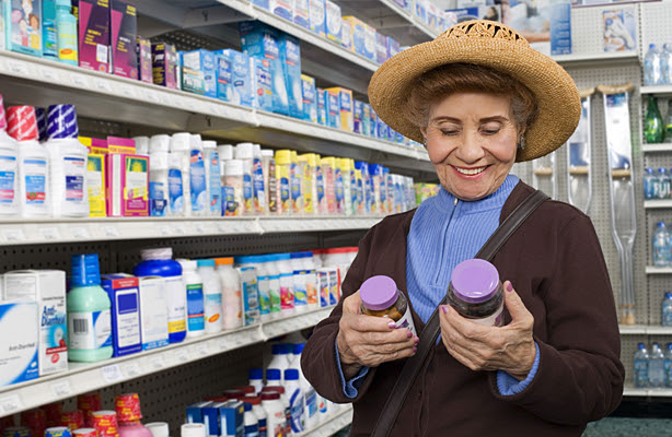 A woman comparing over the counter medication labels.