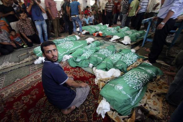 A man sits next to the bodies of Palestinians from Abu Jama'e family, who medics said were killed in an Israeli air strike that destroyed their house, during their funeral at a mosque in Khan Younis in the southern Gaza Strip July 21,  2014.REUTERS-Ibraheem Abu Mustafa