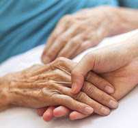 Doctor and older patient holding hands
