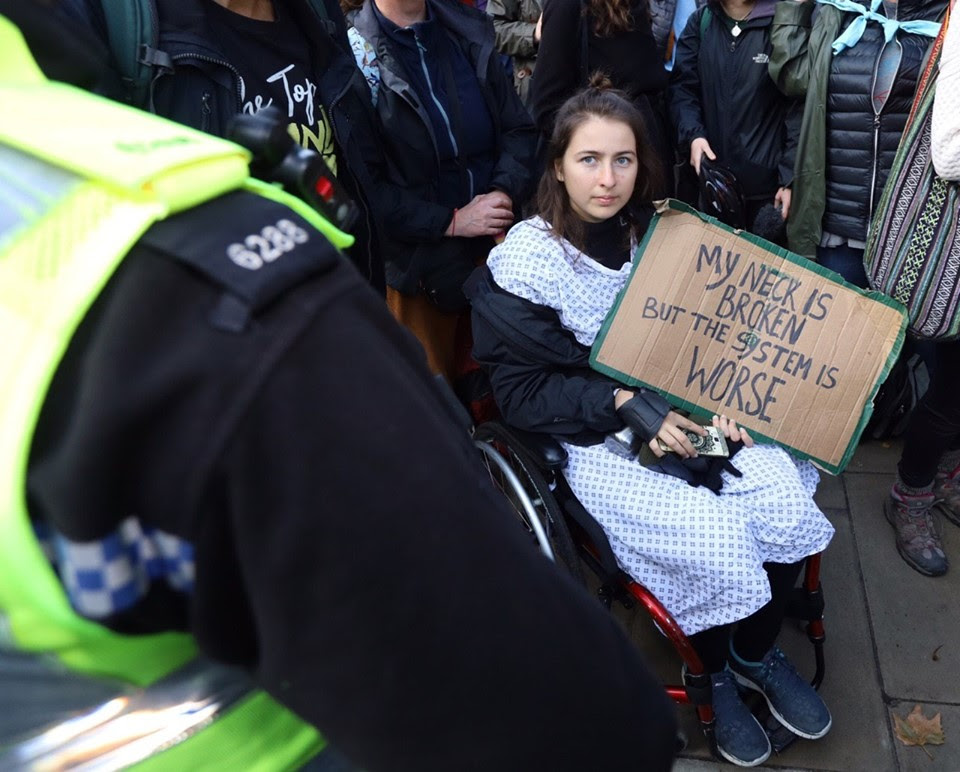 A rebel sat in a wheelchair dressed in a hospital gown. She is holding a sign which says 'My Neck is Broken but the System is Worse'.