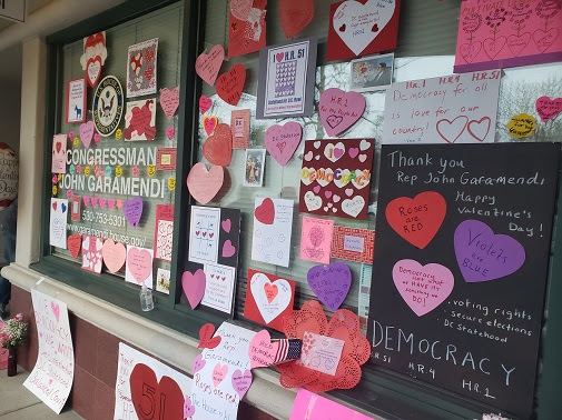 Congressman John Garamendi's Davis office window, covered with handmade valentine's day hearts and posters advocating for HR1, HR4, HR51, voting rights, secure elections, DC statehood