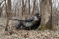 a turkey hunter sitting against a tree