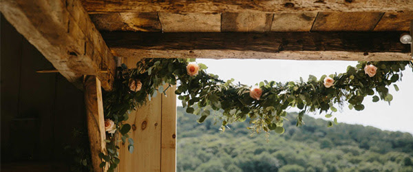 Elegant Floral Garland Drapes the Corner of a Rustic Post-and-Beam Structure